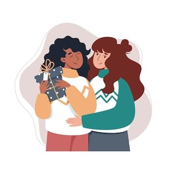 Deux filles serrant et tenant un cadeau