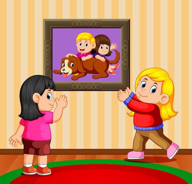 Deux filles tenant le cadre photo et regardant leur photo