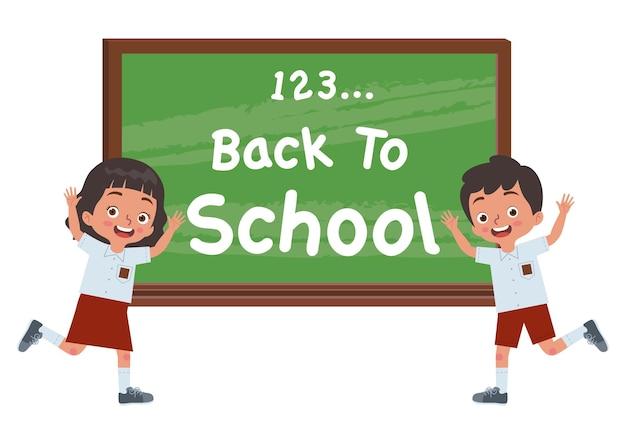 Deux garçons et filles accueillent un autre enfant pour qu'il retourne à l'école devant un tableau noir
