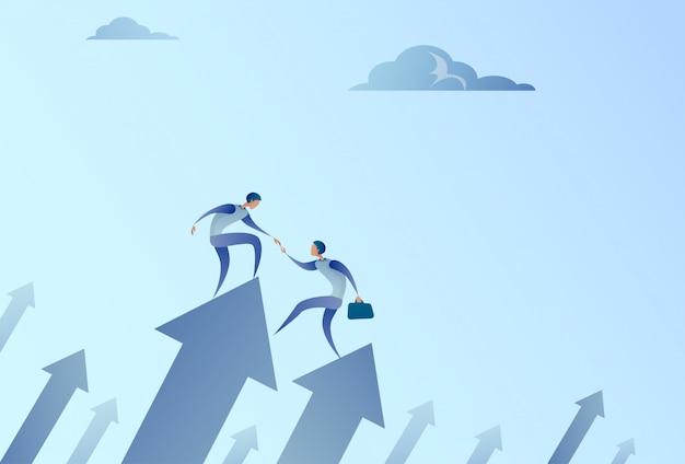 Deux hommes d'affaires se tiennent debout sur la flèche financière se tenant par la main