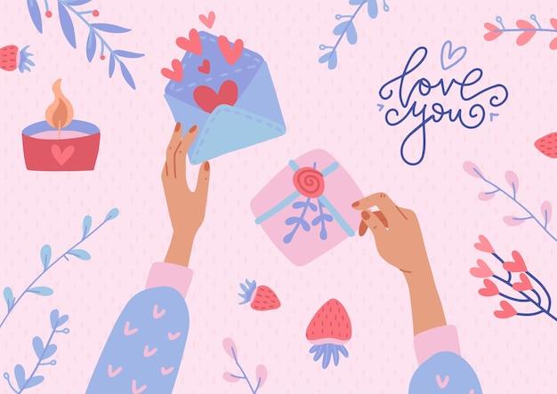 Deux mains tenant l'enveloppe ouverte avec un cœur et une boîte-cadeau décorée