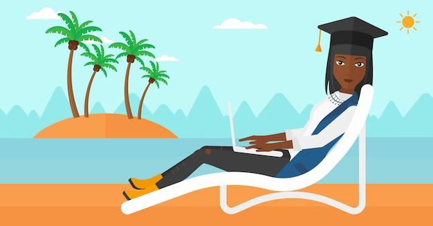 Diplômé allongé sur une chaise longue avec ordinateur portable
