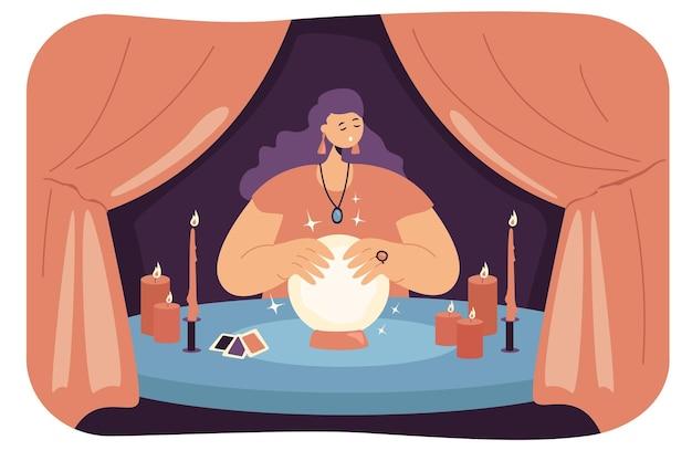 Diseuse de bonne aventure féminine avec boule de cristal dans la tente