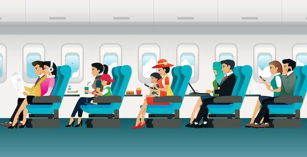 Divers touristes assis sur une chaise à l'intérieur de l'avion.