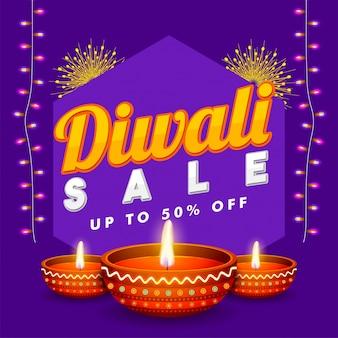 Diwali sale flat 50% bannière avec lampes à huile illuminées.