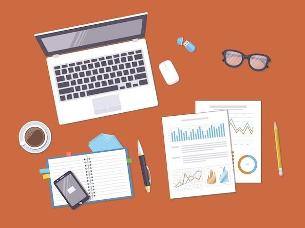 Documents avec tableaux, graphiques, leptop, cahier, téléphone, café, verres. préparation au travail, analyse, rapport, comptabilité, recherche.