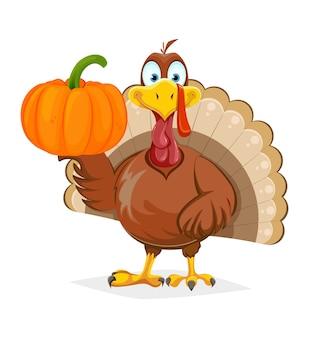 Drôle d'oiseau de dinde de thanksgiving tenant citrouille sur une aile