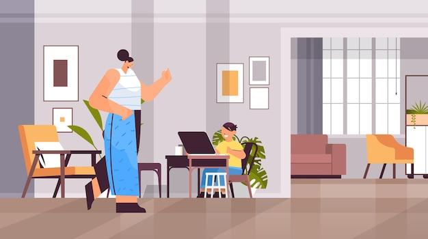 Écolier sur le lieu de travail utilisant un ordinateur portable petit garçon avec une mère faisant ses devoirs