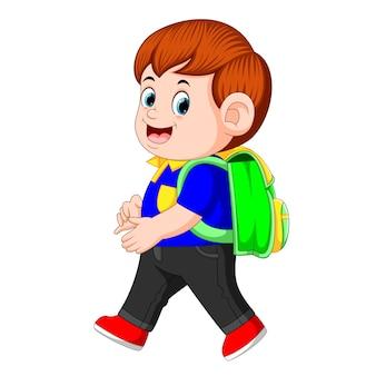Un écolier avec des sacs à dos marchant avec le sourire