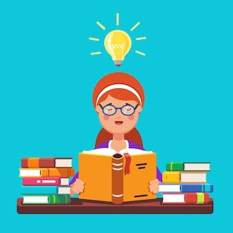 Écolière aux cheveux roux avec un livre de lecture de lunettes