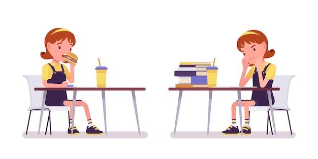 Écolière étudiant et mangeant au bureau