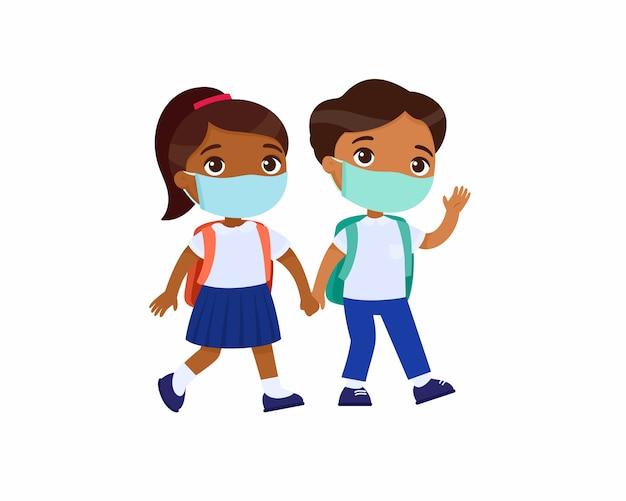 Écolière indienne et écolier allant à l'illustration vectorielle plane de l'école. élèves de couple avec des masques médicaux sur leurs visages, tenant par la main des personnages de dessins animés isolés. deux élèves du primaire