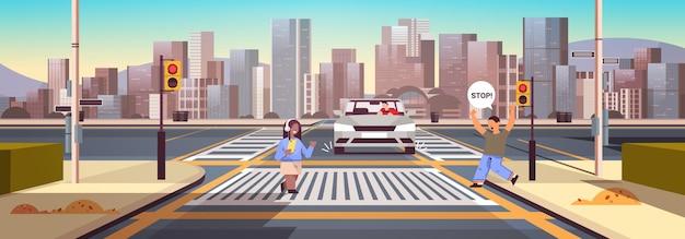 Écolière avec smartphone et casque traversant la route aux feux rouges le conducteur arrête la voiture immédiatement la sécurité routière