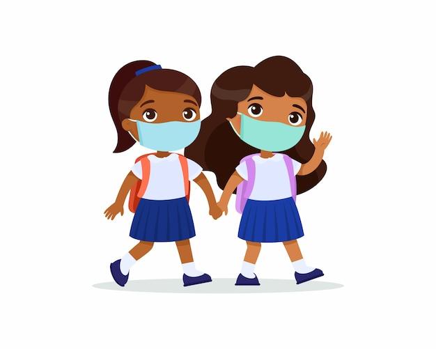 Des écolières indiennes vont à l'école. élèves de couple avec des masques médicaux sur leurs visages tenant par la main des personnages de dessins animés isolés