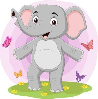 Éléphant heureux de dessin animé avec des papillons dans l'herbe