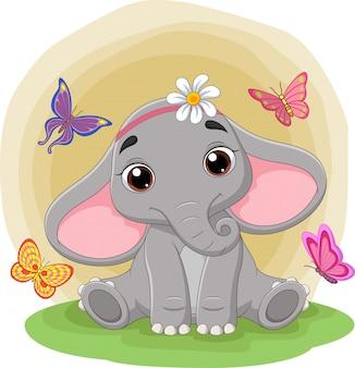 Éléphant mignon bébé assis dans l'herbe parmi les papillons