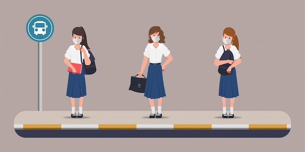 Élève à l'arrêt de bus pour retourner à l'école avec un nouveau concept normal.