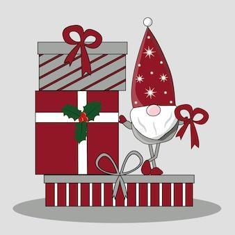 L'elfe du père noël se dresse sur une pile de cadeaux du nouvel an avec du houx et des rubans
