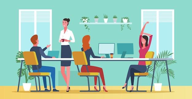 Employés de bureau assis au bureau et se parlant