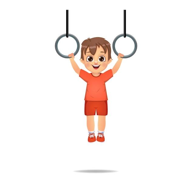 Enfant garçon mignon suspendu avec des anneaux