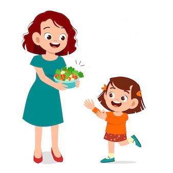 Un enfant heureux et mignon mange une salade