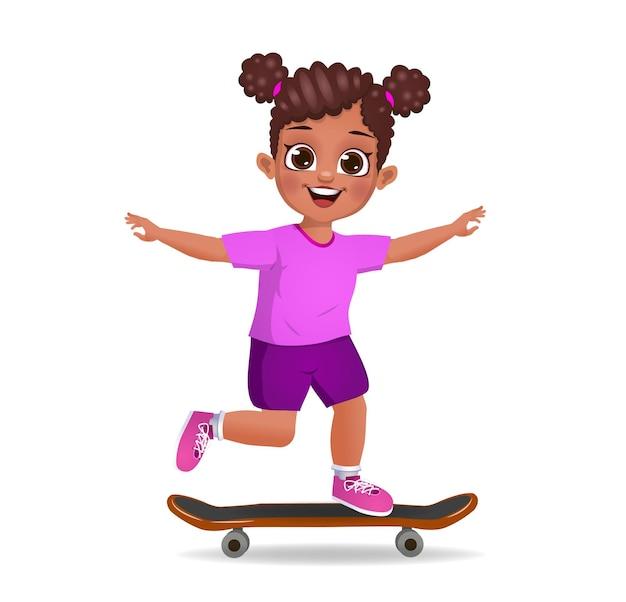 Enfant mignon de fille jouant avec la planche à roulettes