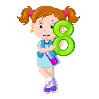 Enfant mignon tenant le ballon avec le numéro huit