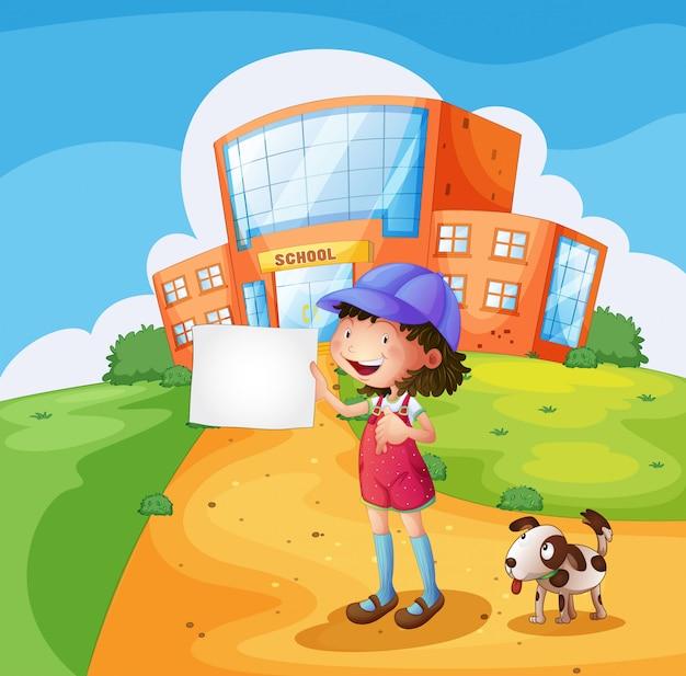 Un enfant avec un morceau de papier devant l'école