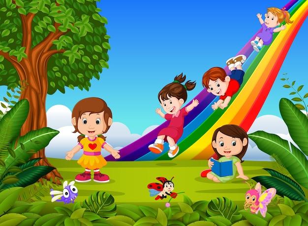 Enfants dessin animé glissant sur l'arc-en-ciel