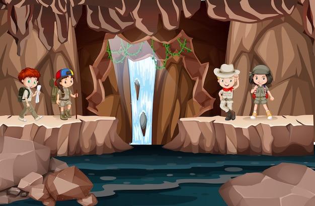 Enfants explorant une grotte avec cascade