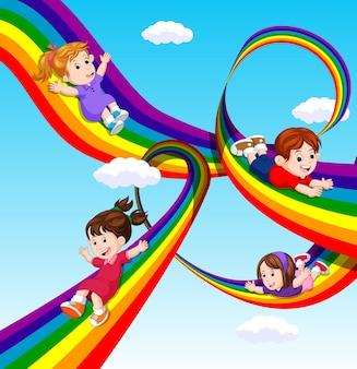 Enfants glissant sur l'arc-en-ciel dans le ciel