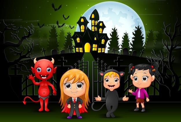 Enfants halloween heureux à l'extérieur avec fond de maison hantée