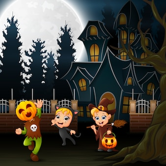 Enfants halloween heureux avec maison effrayante et pleine lune