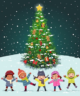 Enfants heureux jouant près de l'arbre de noël sous la neige