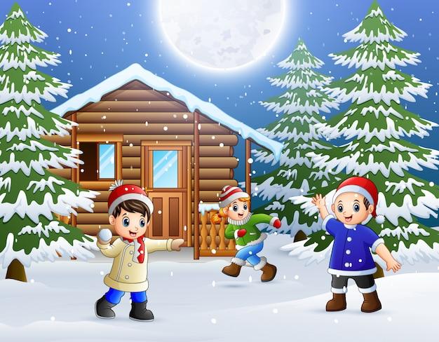 Des enfants heureux jouent devant une maison en bois enneigée