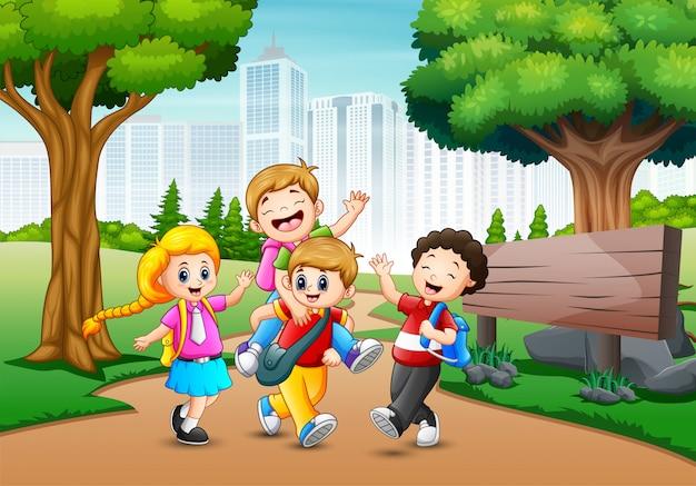 Des enfants heureux à pied passent à travers dans la ville du parc