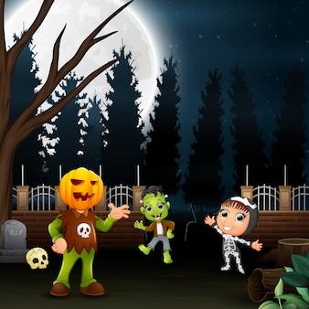 Enfants heureux portant un costume d'halloween au fond de la pleine lune