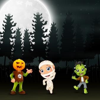 Enfants heureux portant le costume d'halloween dans le jardin