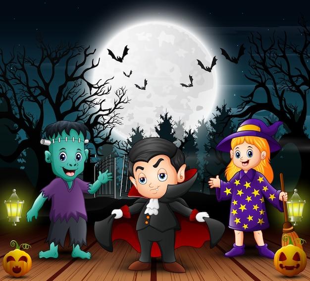 Enfants heureux portant un costume d'halloween dans la nuit
