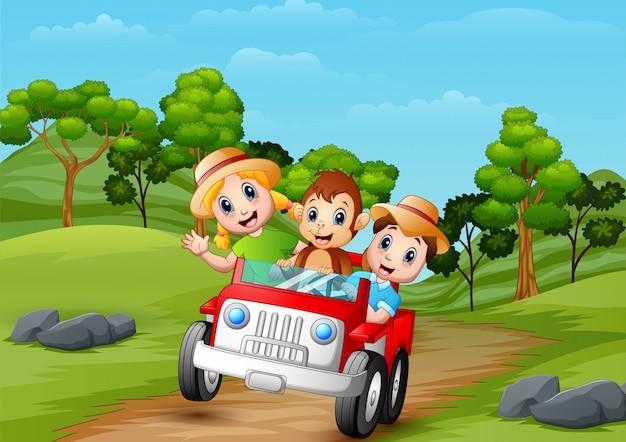 Enfants heureux et singe conduisant une voiture rouge