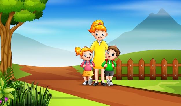 Des enfants heureux vont à l'école avec leur mère