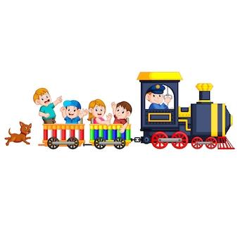 Les enfants et l'ingénieur de la locomotive montent dans le train et le chien les suit