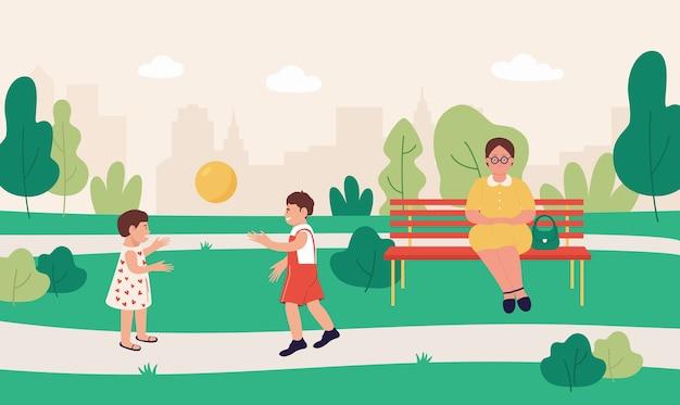 Enfants jouant avec ballon ensemble dans le parc d'été avec mamie assise sur un banc