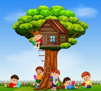 Enfants jouant et lisant le livre dans le jardin sur la cabane dans les arbres