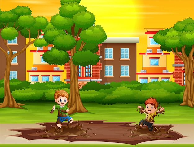 Enfants jouant une flaque de boue dans le parc de la ville