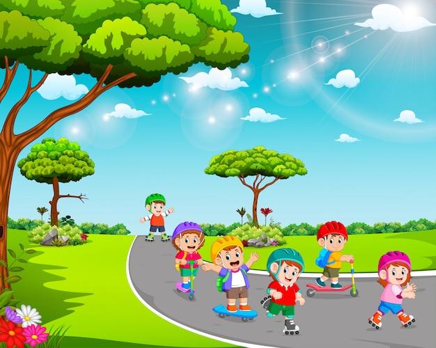 Les enfants jouent sur la route avec le scooter et les patins à roulettes