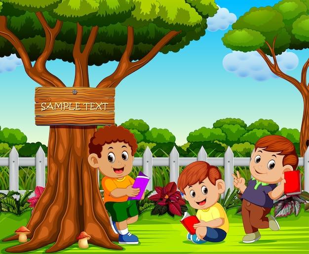 Les enfants lisent et se détendent près de l'arbre