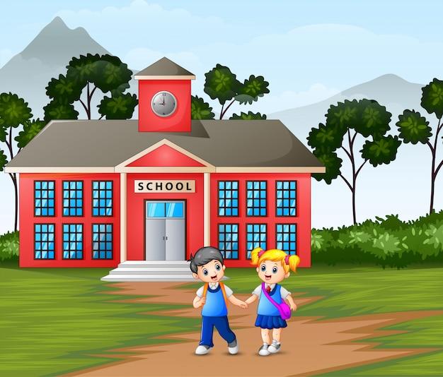 Enfants marchant devant le bâtiment de l'école