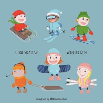 Les enfants avec le matériel de sport jouissant de l'hiver