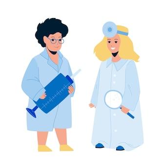Enfants médecins garçon et fille jouent ensemble vecteur. enfants médecins en uniforme médical tenant une seringue et une loupe portant un réflecteur. personnages jouant profession illustration de dessin animé plat